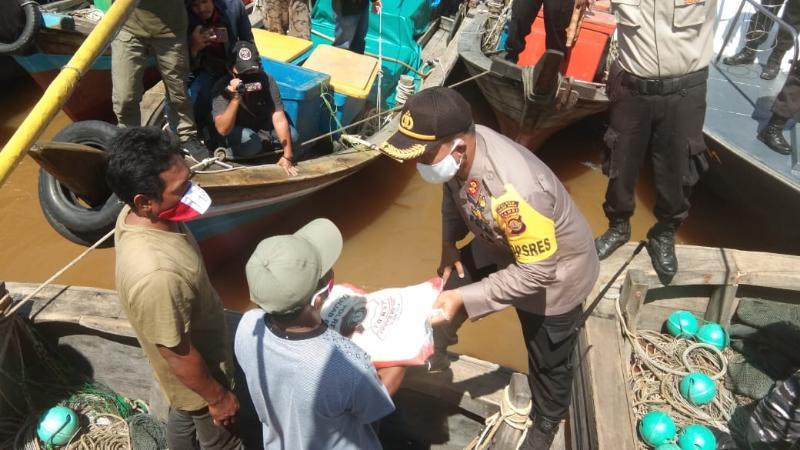 Kapolres Tanjabbar AKBP Guntur Saputo Menyerahkan Bantuan Beras Kapolri kepada para Nelayan di perairan Sungai Pengabuan, Kuala Tungkal. (FOTO : Jambinet ID, Senin 17/08/20)