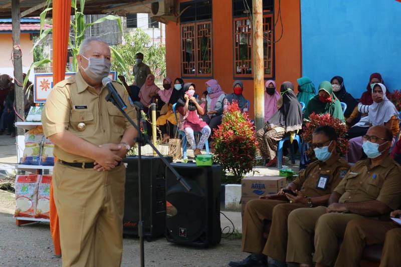 GAMBAR : Bupati H. Safrial Saat Serahkan Secara Eimbolis BSB Tahun 2020 kepada Perwakilan Keluarga PKH