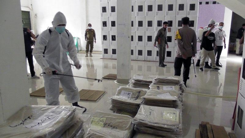 Petugas Kepolisian Polres Tanjab Barat Saat Lakukan Penyemprotan Disinfektan di Gudang Logistis KPUD Tanjab Barat. [FOTO : JambiNET/RES]